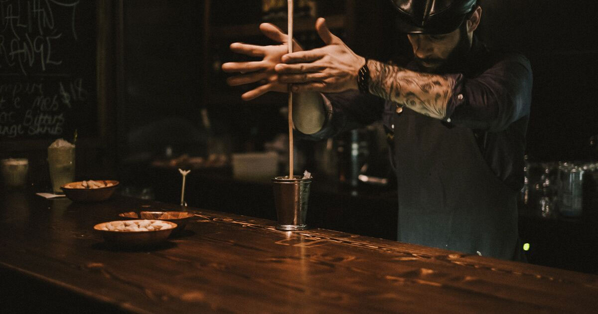 Bartender mixing a cocktail on a old wooden bar