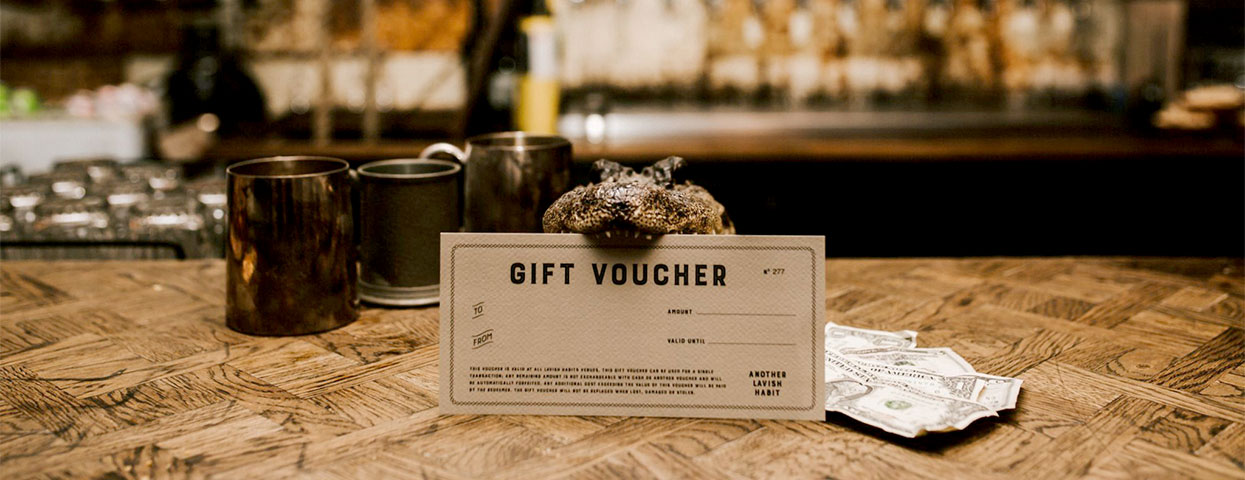 Image of a bar with a small alligator holding a gift certificate in its mouth
