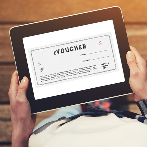 Photo of a woman in a check shirt holding an iPad with a voucher on the screen